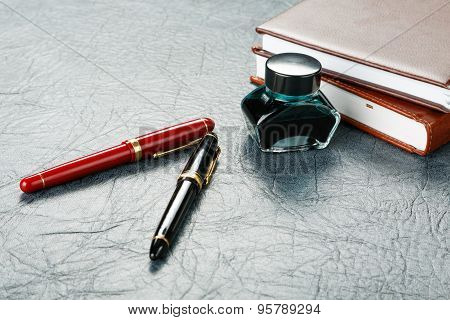 Fountain Pens With Ink And A Pile Of Organizers