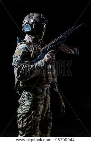 Equipped Soldier Standing In Profile And Holding  Automatic Machine Raised Up