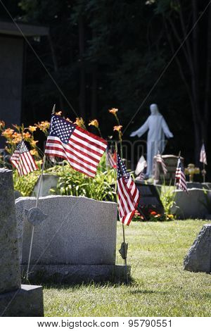 NEWTON, NJ-JULY 2014: American Flags placed next to the gravestones fallen of US Veterans with a statue of Jesus Christ in the background at St Josephs Cemetery in Newton, NJ.