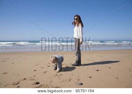 Baby And Mother Walking In Beach