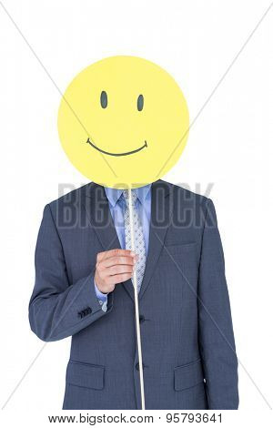 Portrait of a young businessman holding happy smiley faced balloon on white background
