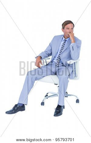 Handsome businessman sitting on a swivel chair against a white screen