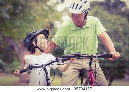 Happy grandfather with his granddaughter on their bike on a sunny day
