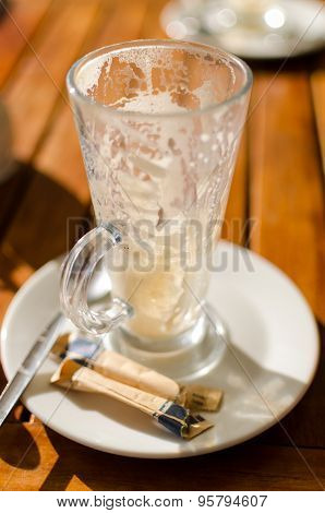 Empty Latte Glass On White Saucer With Spoon And Used Sugar Sachets On Wooden Table Outside. Portait