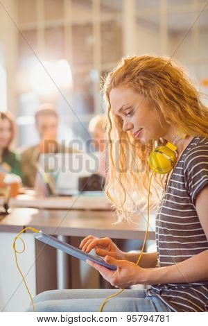 Smiling young woman using digital tablet in the office