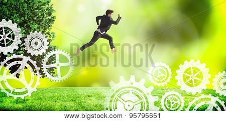 Businessman leaping against field against glowing lights