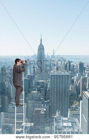 Businessman standing on ladder using binoculars against new york skyline