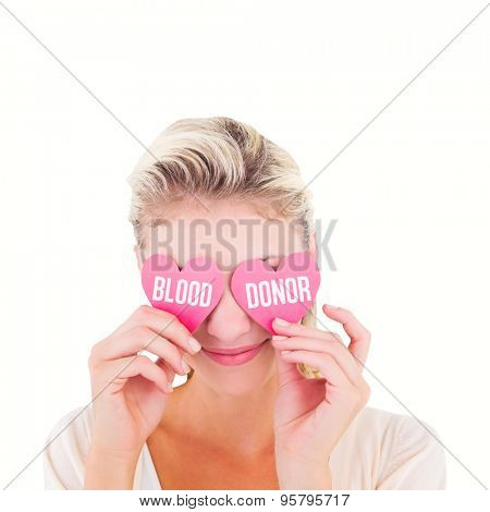 Attractive young blonde holding hearts over eyes against blood donor