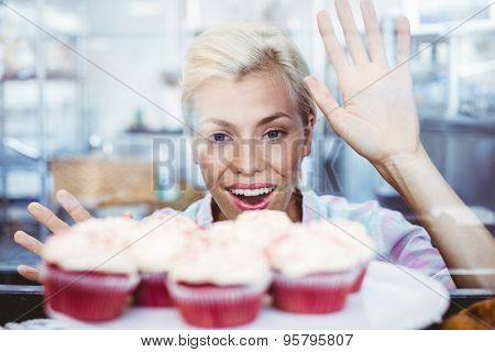 Astonished pretty woman looking at cup cakes at the bakery