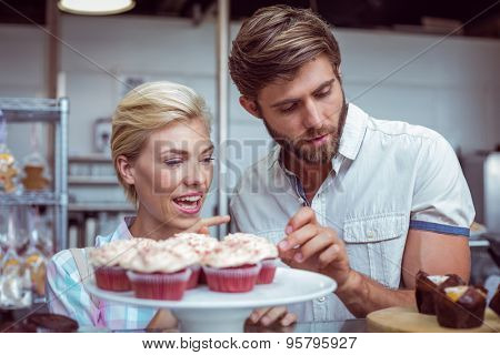Cute couple on a date choosing cakes at the bakery