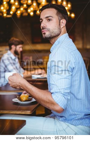 Curious businessman holding a cup of coffee looking away at the cafe