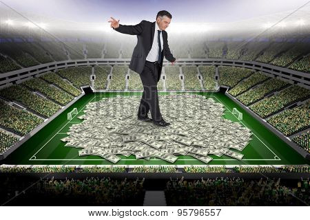 Mature businessman doing a balancing act against pile of dollars