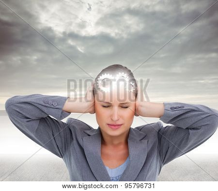 Close up of annoyed tradeswoman covering her ears against grey sky