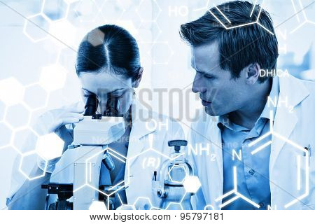 Science graphic against scientists looking through a microscope