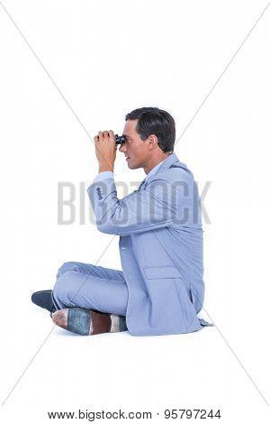 Businessman looking through binoculars on white background