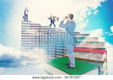 Businessman looking through binoculars against blue sky