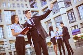 image of secretary  - Young businessman and his secretary standing in front of office building - JPG