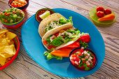 stock photo of chili peppers  - Fish tacos mexican food with guacamole nachos and chili pepper sauce - JPG