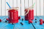 stock photo of mason  - Glass mason jar with raspberry jam and fresh raspberries - JPG
