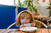 pic of white-milk  - Little White Caucasian Blonde Girl Wearing Pink Summer Hat Sitting at the Table Drinking Warm Milk From White Ceramic Cup Like an Adult in Alfresco Dining Setting and Blue Backdrop - JPG