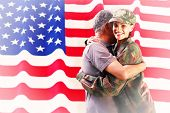 foto of reunited  - Solider reunited with father against rippled us flag - JPG