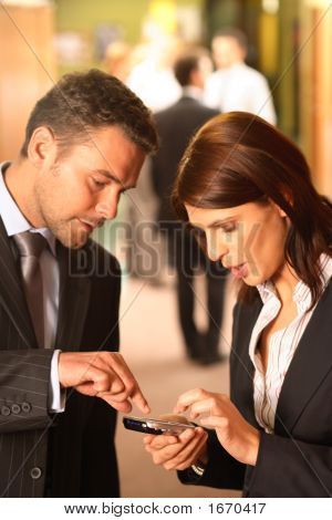 Business Couple Using Cellphone