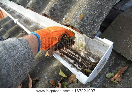 hand. Roof Gutter Cleaning Tips. Clean Your Gutters Before They Clean ...