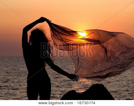 Girl with voile on sunset background.