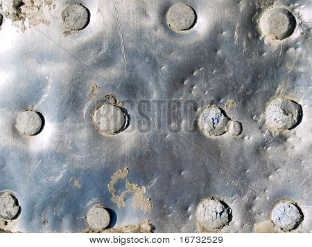 Riveted metal surface closeup background.