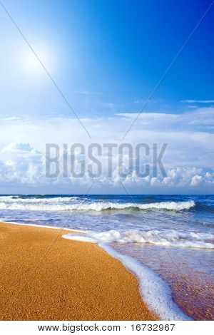 Sea, yellow sand and bright sun on blue sky.