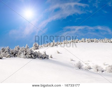 Snowy landscape with sun on blue sky.
