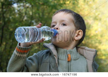 fünf Jahre alter Junge trinken Mineralwasser - Ruhe im Wald
