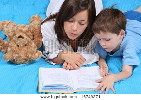 mother and five years old boy reading book - good night