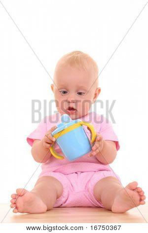 Retrato de 10 meses Bebé niña con taza de bebé aislado en blanco