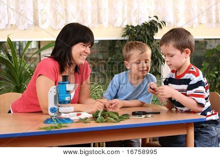 biology lesson in preschool - teacher and two boys