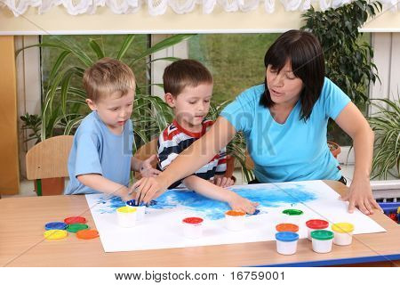 teacher two preschoolers and fingerpainting - education