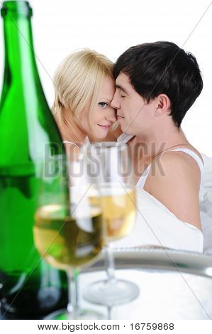 Young couple drinking champagne in bed