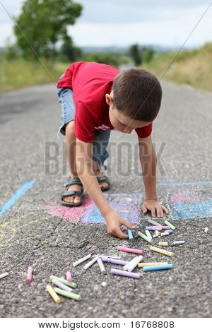 8 years old boy drawing with sidewalk chalk - family and kids