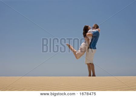 Young Couple Hugging On The Beach
