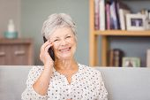 Portrait of senior woman using mobile phone at home poster
