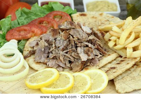 Plate of traditional Greek gyros or Turkish kebab with meat, fried potatoes, tomato and onion