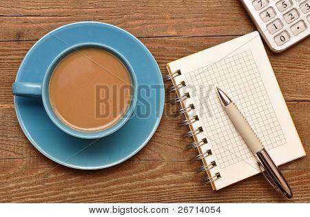 Koffiekopje, spiraal notebook en pen op de oude houten tafel