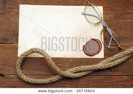 Old paper with a wax seal on a wood background
