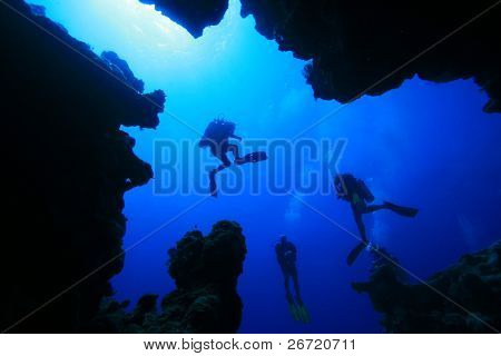 Diver silhouettes from in an underwater canyon