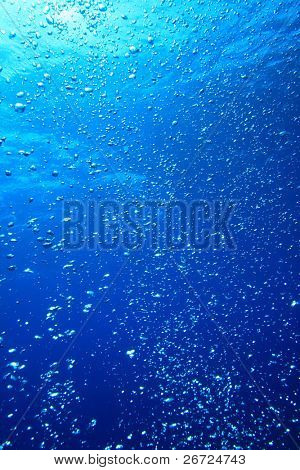Air bubbles float up through blue sea water