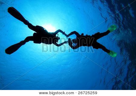 Scuba Divers in clear blue water, silhouetted against sun