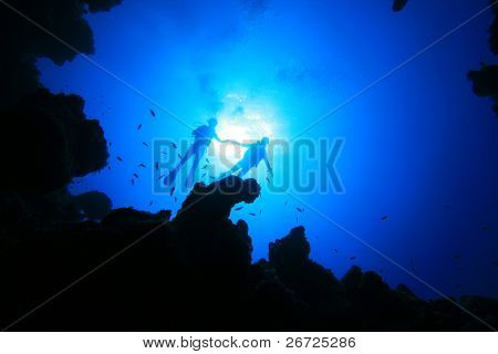 Scuba Diving couple about to descend into an underwater canyon