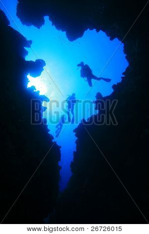 Scuba Divers descend into underwater cavern, silhouetted against sun