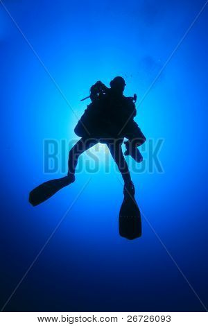 Technical Diver with several cylinders silhouetted against sun after a deep exploration dive in the ocean
