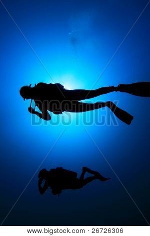 Underwater image of Scuba Diver silhouetted against sun
